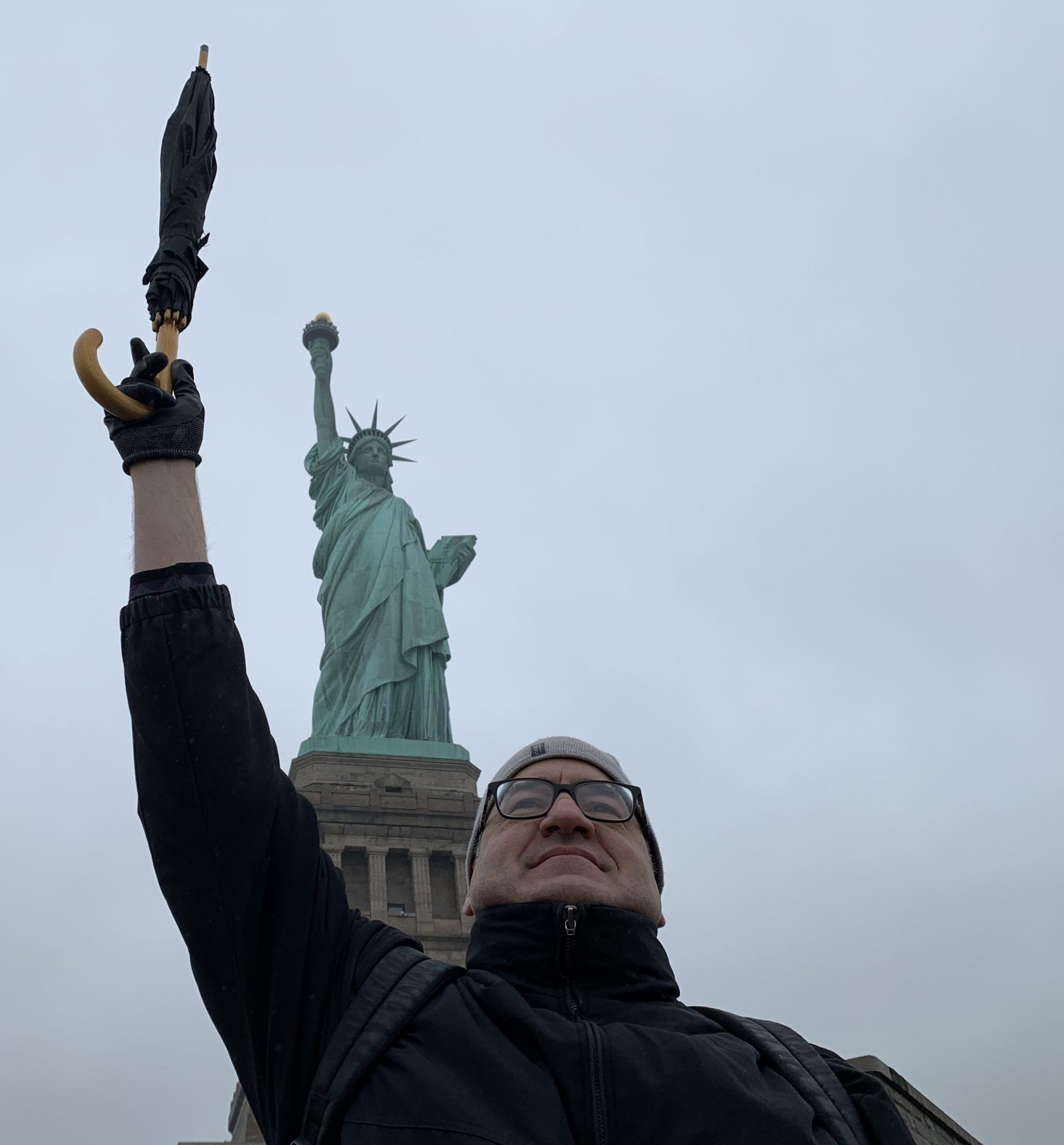 The author standing in front of the Statue of Liberty on a rainy, uncrowded day in February.